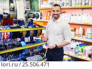 Купить «Man next to showcase with metallic chains», фото № 25506471, снято 20 февраля 2019 г. (c) Яков Филимонов / Фотобанк Лори