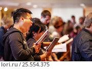 Купить «An Asian American parishioner yawns while singing a hymn during mass at a Laguna Niguel, CA, Catholic church.», фото № 25554375, снято 24 апреля 2016 г. (c) age Fotostock / Фотобанк Лори