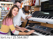Купить «Happy couple selecting synthesizer», фото № 25564867, снято 11 февраля 2016 г. (c) Татьяна Яцевич / Фотобанк Лори