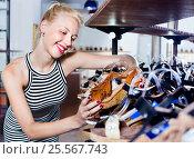 Купить «Glad woman shopping pair of new shoes», фото № 25567743, снято 22 января 2020 г. (c) Яков Филимонов / Фотобанк Лори