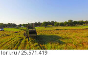 Купить «Combine Harvester Leaving Hay On Field After Mowing», видеоролик № 25571419, снято 27 июля 2015 г. (c) Владимир Кравченко / Фотобанк Лори