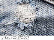 Купить «close up of hole on shabby denim or jeans clothes», фото № 25572367, снято 15 сентября 2016 г. (c) Syda Productions / Фотобанк Лори