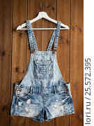 denim or jeans overalls with hanger on wood. Стоковое фото, фотограф Syda Productions / Фотобанк Лори