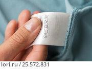 Купить «hand holding label with users manual of clothing», фото № 25572831, снято 15 сентября 2016 г. (c) Syda Productions / Фотобанк Лори