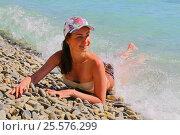 Купить «Красивая темноволосая девушка в купальнике, накрываемая морской волной, лежит на галечном пляже», эксклюзивное фото № 25576299, снято 12 июня 2016 г. (c) Артём Крылов / Фотобанк Лори