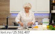 Купить «Housewife pensioner prepares dietary dinner. Grilled trout on a pair and vegetable garnish.», видеоролик № 25592407, снято 10 февраля 2017 г. (c) Tatiana Kravchenko / Фотобанк Лори