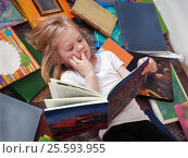 Купить «Child and a lot of books around. Little girl reading a book lying on the floor», фото № 25593955, снято 15 октября 2019 г. (c) Ирина Козорог / Фотобанк Лори