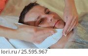 Купить «Man getting massage in the spa centre. Drying facial wipes. Massage the face and neck.», видеоролик № 25595967, снято 20 февраля 2017 г. (c) Mikhail Davidovich / Фотобанк Лори