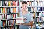 teenage boy with book pile in shop, фото № 25596847, снято 16 сентября 2016 г. (c) Яков Филимонов / Фотобанк Лори