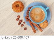 Coffee with crema in blue cup and snacks. Hazelnuts, cookie, muffin, cinnamon and coffee, top view. Стоковое фото, фотограф Евгений Пидеркин / Фотобанк Лори