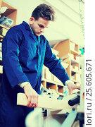 Купить «Man processing plank at workshop», фото № 25605671, снято 7 ноября 2016 г. (c) Яков Филимонов / Фотобанк Лори