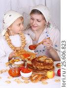 Мама с дочкой едят блины с красной икрой за праздничным столом. Масленица. Стоковое фото, фотограф Марина Володько / Фотобанк Лори