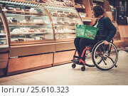 Купить «Disabled woman in a wheelchair in a grocery store», фото № 25610323, снято 15 августа 2018 г. (c) Andrejs Pidjass / Фотобанк Лори