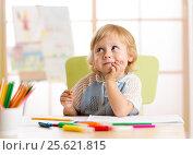 Купить «Smiling kid drawing with color pencils in day care center», фото № 25621815, снято 17 декабря 2016 г. (c) Оксана Кузьмина / Фотобанк Лори