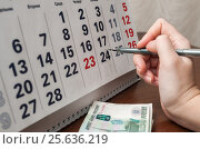 Купить «Оплата кредита по сроку. Шариковая ручка в руке и деньги на фоне календаря», эксклюзивное фото № 25636219, снято 6 февраля 2017 г. (c) Игорь Низов / Фотобанк Лори