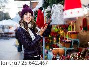 Купить «Girl buying Christmas floral compositions», фото № 25642467, снято 22 декабря 2016 г. (c) Яков Филимонов / Фотобанк Лори