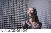 Купить «Attractive singer with headphones», видеоролик № 25664007, снято 20 июня 2019 г. (c) Raev Denis / Фотобанк Лори