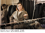 Купить «Woman trying on sheepskin coat in women's cloths store», фото № 25665235, снято 23 февраля 2020 г. (c) Яков Филимонов / Фотобанк Лори