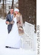 Купить «Жених и невеста в зимнем парке рядом с белой железной скамейкой», фото № 25696399, снято 26 февраля 2017 г. (c) Кекяляйнен Андрей / Фотобанк Лори