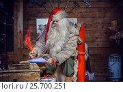 Санта-Клаус с пышной седой бородой подписывает письмо в своей избушке, сидя на красном троне. Стоковое фото, фотограф Борис Смирин / Фотобанк Лори