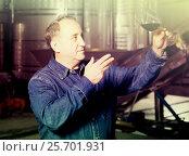 Купить «Worker of winery costs with glass of red wine near tanks», фото № 25701931, снято 12 октября 2016 г. (c) Яков Филимонов / Фотобанк Лори