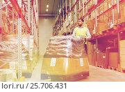 Купить «man carrying loader with goods at warehouse», фото № 25706431, снято 9 декабря 2015 г. (c) Syda Productions / Фотобанк Лори