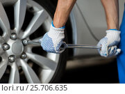 Купить «mechanic with screwdriver changing car tire», фото № 25706635, снято 1 июля 2016 г. (c) Syda Productions / Фотобанк Лори