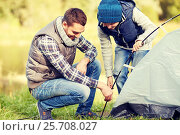 Купить «happy father and son setting up tent outdoors», фото № 25708027, снято 27 сентября 2015 г. (c) Syda Productions / Фотобанк Лори