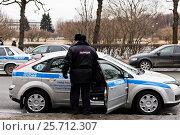 Сотрудник полиции у служебного автомобиля (2017 год). Редакционное фото, фотограф Евгений Кашпирев / Фотобанк Лори