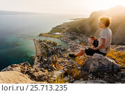 A young guy in a T-shirt and shorts sits high on a rock against the background of the sea and looks out into the distance. Стоковое фото, фотограф Андрей Орехов / Фотобанк Лори