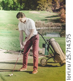 Купить «Man playing golf is going to hit ball at golf course», фото № 25714575, снято 14 ноября 2018 г. (c) Яков Филимонов / Фотобанк Лори