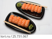 Salmon sushi, wooden sticks and wasabi on two black ceramic plates of a bean-shaped form, фото № 25731067, снято 8 марта 2017 г. (c) Anatoly Timofeev / Фотобанк Лори
