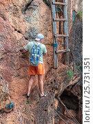Купить «Турист пробирается вдоль отвесной скалы к вертикальной лестнице на смотровую площадку в горах. Королевство Таиланд, провинция Краби, полуостров Рейли (Railay)», фото № 25731351, снято 30 января 2017 г. (c) Владимир Сергеев / Фотобанк Лори