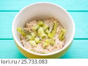 Купить «Oatmeal with milk and kiwi in a yellow bowl», фото № 25733083, снято 5 марта 2017 г. (c) Дегтярева Виктория / Фотобанк Лори