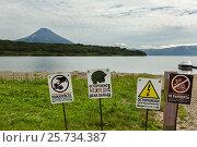 Купить «Signs warn of the danger of meeting tourists with bears on background of Kurile Lake and Ilyinsky volcano», фото № 25734387, снято 13 августа 2016 г. (c) Юлия Машкова / Фотобанк Лори