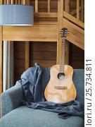 Купить «Cozy living room with guitar on the sofa», фото № 25734811, снято 18 февраля 2016 г. (c) Дарья Петренко / Фотобанк Лори