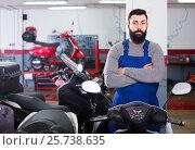 Купить «man worker displaying various motorcycles in workshop», фото № 25738635, снято 21 сентября 2019 г. (c) Яков Филимонов / Фотобанк Лори
