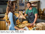 Купить «Smiling female customer receiving a parcel from bakery staff at counter», фото № 25745631, снято 4 октября 2016 г. (c) Wavebreak Media / Фотобанк Лори