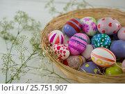 Купить «Basket with painted Easter eggs on wooden background», фото № 25751907, снято 10 января 2017 г. (c) Wavebreak Media / Фотобанк Лори