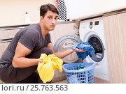 Купить «Young husband man doing laundry at home», фото № 25763563, снято 10 октября 2016 г. (c) Elnur / Фотобанк Лори