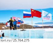 Купить «Дружба народов. Русский мужчина и китайская женщина стоят на ледяных кубиках рядом с государственными флагами», фото № 25764275, снято 11 марта 2017 г. (c) Виктор Никитин / Фотобанк Лори