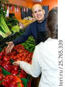 Купить «Friendly worker selling vegetables to female customer», фото № 25765339, снято 17 ноября 2019 г. (c) Яков Филимонов / Фотобанк Лори