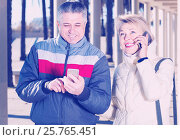 Купить «cheerful husband and wife go nearby with each other and speak by mobile phone», фото № 25765451, снято 20 августа 2019 г. (c) Яков Филимонов / Фотобанк Лори
