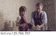 Купить «Boy with teacher in the pottery», видеоролик № 25766707, снято 6 апреля 2020 г. (c) Raev Denis / Фотобанк Лори