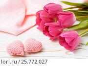 Пара вязанных розовых сердец и букет свежих тюльпанов на деревянном столе. Стоковое фото, фотограф Елена Руй / Фотобанк Лори