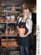 Купить «Cheerful woman potter carrying ceramic vessels», фото № 25772451, снято 20 октября 2018 г. (c) Яков Филимонов / Фотобанк Лори