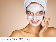 Купить «Young woman applying moisturizer cream on her face. Photo of smiling woman receiving spa treatments. Grooming himself», фото № 25781595, снято 13 мая 2016 г. (c) Роман Егошин / Фотобанк Лори