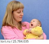 Купить «Зевающий младенец на руках у молодой женщины на синем фоне», фото № 25784035, снято 19 ноября 2014 г. (c) Ирина Борсученко / Фотобанк Лори