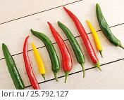Chili peppers are in a row - yellow, green and red chili pepper. Стоковое фото, фотограф Денис Иванов / Фотобанк Лори