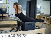 Купить «Determined woman practicing stretching exercise on reformer», фото № 25793731, снято 7 октября 2016 г. (c) Wavebreak Media / Фотобанк Лори